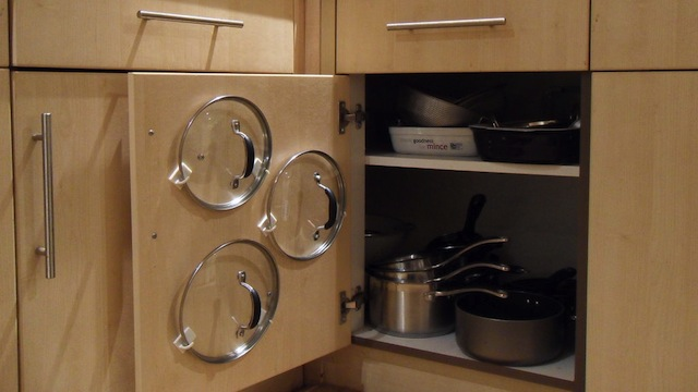 style use adhesive hooks to organize your pot lids and save