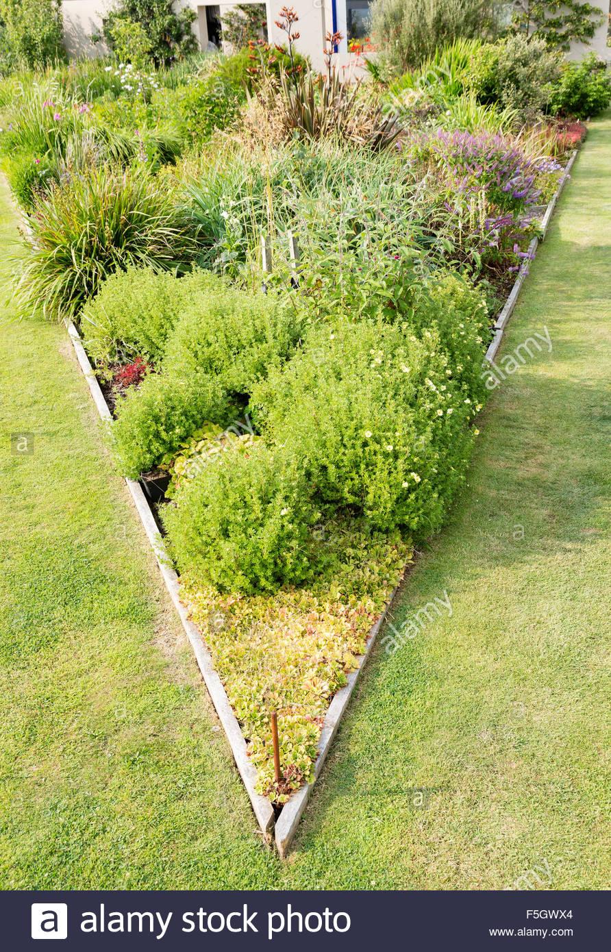 best triangular raised flower bed on large garden lawn stock